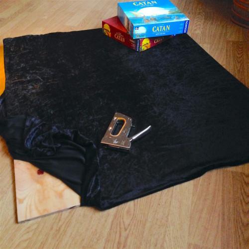 Ett svart tyg spändes över en plywoodskiva med hjälp av häftpistol