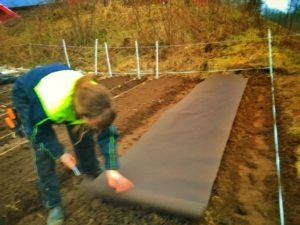 Hanna rullar ut geotexduk över odlingsbädden
