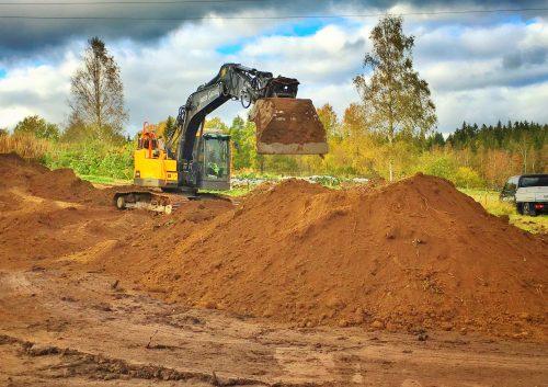 Grävmaskinen flyttar jordhögen på Broaker